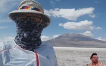 podróżnik w kapeluszu z zasłoniętą chustką twarzą na tle pustynnych szczytów