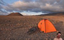 pustynny krajobraz, w tle zachmurzone niebo, na pierwszym planie z prawej strony pomarańczowy namiot i leżący obok niego rower