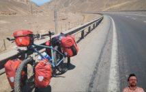 widok drogi przez obszar pustynny, w tle szczyty górskie, przy szosowej balustradzie po lewej srtonie stoi oparty rower z bagażem