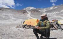 panorama pustynna z ośnieżonym szczytem w tle. Centralnie namiot turystyczny, na pierwszym planie podróżnik ubrany w kurtkę i kapelusz