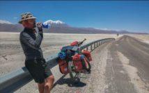 widok drogi przez obszar pustynny, w tle szczyty górskie, przy szosowej balustradzie po lewej srtonie opiera się mężczyzna pijący wodę z bidonu, obok niego stoi rower z bagażem