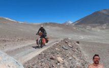 szutrowa droga pod górę, po której mężczyzna jedzie rowerem