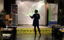 bibliotekarka na tle sceny i ekranu z wyświetloną prezentacją, po prawej roll-up z logo nowotomyskiej biblioteki, po prawej logo programu Równać Szanse. Na pierwszym planie po obu stronach stoliki, przy których siedzi młodzież biorąca udział w projekcie