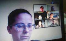 Kobieta w okularach, z tyłu widoczny ekran komputera z 6 osobami, którzy biorą udział w spotkaniu online.