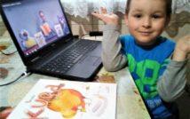 zdjęcie przedstawia po lewej stronie otwarty laptop z odtwarzanymi warsztatami.po prawej stronie uśmiechnięty chłopiec.na dole zdjęcia leży książka na stole pt. Kura, co tyła na diecie