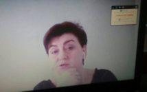 Kobieta prowadząca spotkanie online, w uchu ma słuchawkę, z tyłu ekran.