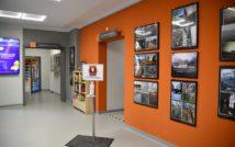 hol biblioteki, po prawej stronie ramy z konkursowymi zdjęciami, centralnie stanowisko do dezynfekcji rąk, po lewej monitor reklamowy