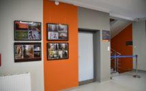 hol biblioteki, po prawej stronie ramy z konkursowymi zdjęciami, po prawej barierka zagradzająca