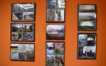 ściana, na któej są powieszone ramy z konkursowymi fotografiami ziemi nowotomyskiej
