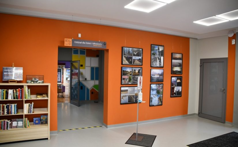 hol biblioteki, po lewej półka z ksiazkami, po prawej ramy ze zdjęciami konkursowymi
