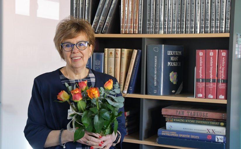 Kobieta w okularach z bukietem kwiatów w ręku. Z tyłu półki z książkami.
