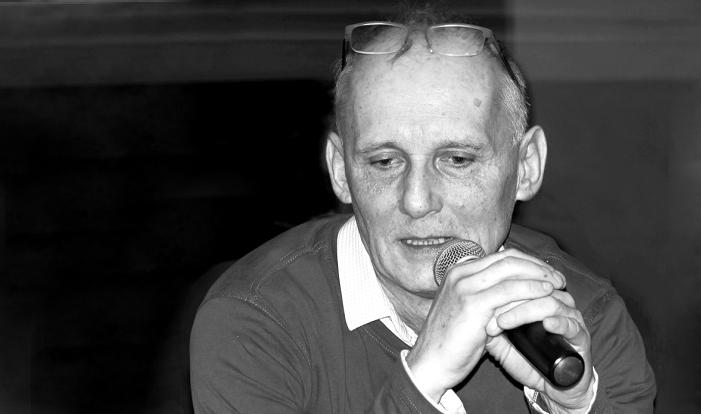 czarno-biała fotografia siedzącego mężczyzny z mikrofonem w ręce