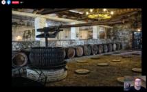 Piwnica. Zbiornik do robienia wina, z tyłu beczki, u góry lampa. W prawym dolnym rogu dwoje ludzi w okularach.