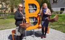 Zdjęcie bibliotecznego skweru, na krórym stoi półka bookcrossingowa w kształcie litery B. Wokół placyku wyłożonym kostką polbruk widac zieleń miejską. Dwie bibliotekarki stoją obok półki
