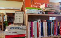 Fotografia regału z ksiażkami. Na książkach stoi czytnik