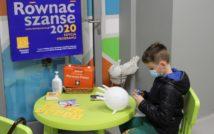 Chłopiec siedzący bokiem przy stoliku. W ręku trzyma pisak. Na stoliku: balon, karty, książki, płyn do dezynfekcji, apteczka pierwszej pomocy w koszyczku. Na drzwiach plakat z napisem: Równać szanse 2020. Poniżej napis: edycja programu. W lewym dolnym rogu logo, niżej napis: Równać szanse.