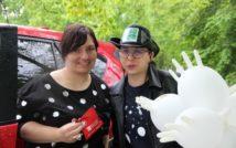 Dwie uśmiechnięte kobiety. Kobieta z lewej strony trzyma w ręku mini apteczkę. Kobieta z prawej strony ma okulary i kapelusz z logo biblioteki. W ręku ma trzy balony. Za kobietami fragment samochodu i drzewa.