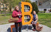 Zdjęcie bibliotecznego skweru, na krórym stoi półka bookcrossingowa w kształcie litery B. Wokół placyku wyłożonym kostką polbruk widac zieleń miejską. Obok półki, po lewej stronie stoi dyrektor MiP Biblioteki Publicznej w Nowym Tomyślu, po prawej siedzi jedna z bibliotekarek