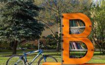 Zdjęcie bibliotecznego skweru, na króeym stoi półka bookcrossingowa w kształcie litery B. Wokół placyku wyłożonym kostką polbruk. Przy regale, po lewej stronie stoi rower