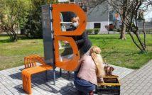 Zdjęcie bibliotecznego skweru, na krórym stoi półka bookcrossingowa w kształcie litery B. Wokół placyku wyłożonym kostką polbruk widać zieleń miejską. Dwie bibliotekarki układają w niej książki
