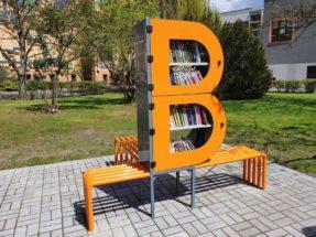 Zdjęcie bibliotecznego skweru, na króeym stoi półka bookcrossingowa w kształcie litery B. Wokół placyku wyłożonym kostką polbruk widac zieleń miejską