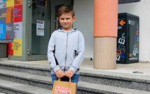 uśmiechnięty chłopiec.w obu rękach trzyma papierową torbę z nagrodą w środku.w tle front biblioteki