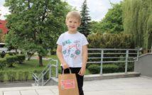 uśmiechniety chłopiec w swojej prawej ręce trzyma nagrodę za udział w konkursie. w tle zieleń miejska.