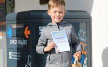 uśmiechnięty chłopiec.w lewej ręce trzyma papierową torbę z nagrodą w środku.w prawej trzyma dyplom za udział w konkursie.w tle wrzutnia biblioteczna.