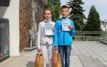 Uśmiechnięta dziewczynka i chłopiec.trzymają w swojej lewej ręce dyplom.w tle taras biblioteki.