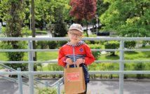 uśmiechnięty chłopiec w czapce i okularach. w obu rękach trzyma papierową torbę z nagrodą w środku.w tle zieleń miejska