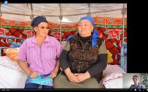 Dwie kobiety siedzą na łóżku w chustkach na głowach. Za nimi kolorowa makata we wzory. W prawym dolnym rogu kobieta, która mówi. Z tyłu kwiat.