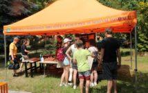 """Zdjęcie przedstawiające ludzi, na świeżym powietrzu i tekst na namiocie w kolorze pomarańczowym """"MIEJSKA POWIATOWA BIBLIOTEKA PUBL CZNA w NOWYM TOMYŚLU nac se"""""""