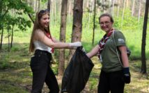 Dwie młode, uśmiechnięte kobiety stojące w lesie. Jedna trzyma worek na śmieci. Druga sięga do worka.
