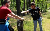 Dwóch młodych mężczyzn w lesie. Jeden trzyma otwarty worek na śmieci. Drugi mężczyzna ma wyciągniętą rękę.
