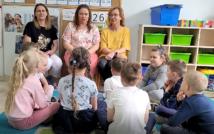 w centralnej części zdjęcia na krzesłach siedza trzy kobiety, wokół nich siedzą na podłodze dzieci. W tle szafki i zabawki sali przedszkolnej.