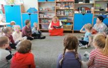 Na podłodze siedzi kobieta i trzyma w rękach książkę.Wokół niej w kółeczku siedzą dzieci. W tle szafki i zabawki sali przedszkolnej.