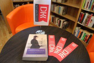 na pierwszym planie, na stoliku, książka i zakładki klubu DKK, w tle regał z książkami i pomarańczowy fotel