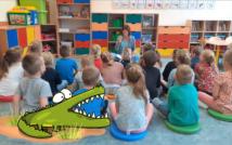 na podłodze siedzą plecami dzieci, przed nimi nauczycielka czyta wierszyki.W tle szafki i zabawki sali przedszkolnej.