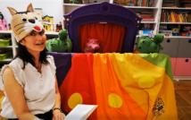 lewa strona zdjęcia: na podłodze siedzi kobieta w czapce kota na głowie, trzyma w rękach otwartą książkę. Za nią teatrzyk pacynkowy, a w tle szafki i zabawki sali przedszkolnej.