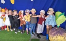 """od prawej strony zrobiona z krepy i papieru wielka rzepa.Za nią stoją """"gęsiego"""" dzieci. Pierwsze dziecko ubrane jest koszulę w kratę, ma doklejone wąsy i na głowie kapelusz.za nim dziewczynka w okularach w sweterku i spodnicy do kostek, w okularach i z chusta na głowie, za nią chłopiec w koszulce i w kapeluszu.potem chopiec w dźokejce i w krótkich spodenkach. za nim chłopiec w kostiumie psa, potem dwie dziewczynki ubrane za koty.dalej dwie dzieczynki przebrane za kurczaczki."""