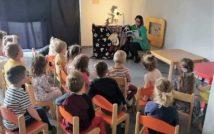 dzieci siedzą plecami na krzesłacch.Przed nimi pani nauczycielka czyta książkę.Za nią teatrzyk cieni.