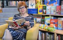 lewa strona zdjęcia: na fotelu siedzi kobieta w sukience i w okularach, trzyma otwartą książkę.W tle okładki książek.