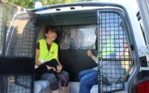Dwie uśmiechnięte dziewczyny w radiowozie policyjnym, siedzące za kratami, w kamizelkach odblaskowych.