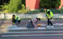 Trzy osoby w kamizelkach odblaskowych, przed przejściem dla pieszych na świeższym powietrzu. Dwie osoby klęczą i malują z tej pozycji po chodniku, jedna osoba stoi w pozycji pół zgiętej. W tle murek i zieleń.