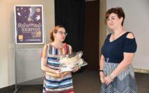 Dwie kobiety, które stoją na tle plakatu Równać Szanse, w budynku. Jedna trzyma upominek w dłoni.