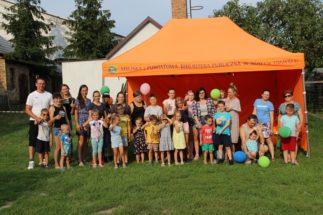 Grupa osób, dorosłych i dzieci, stojących przed pomarańczowym namiotem z napisem MIEJSKA I POWIATOWA BIBLIOTEKA PUBLICZNA W NOWYM TOMYŚLU
