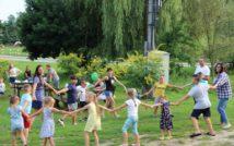 Zdjęcie przedstawia grupę osób - dzieci i dorosłych bawiących się w kółku i trzymających się za ręce. W tle widoczne inne osoby, stoły, drzewa, ulica