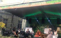 Siedem osób dorosłych siedzi na scenie z otwartymi książkami w rękach. U góry napis: Nowotomyski Jarmarek.