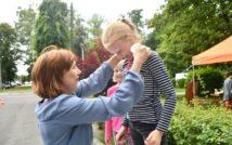 Dwie osoby, kobieta i dziecko na świeżym powietrzu. Kobieta zakłada dziecku medal.