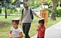 Trzy osoby na świeżym powietrzu: mężczyzna i dwoje dzieci. Dzieci niosą na głowach książki.